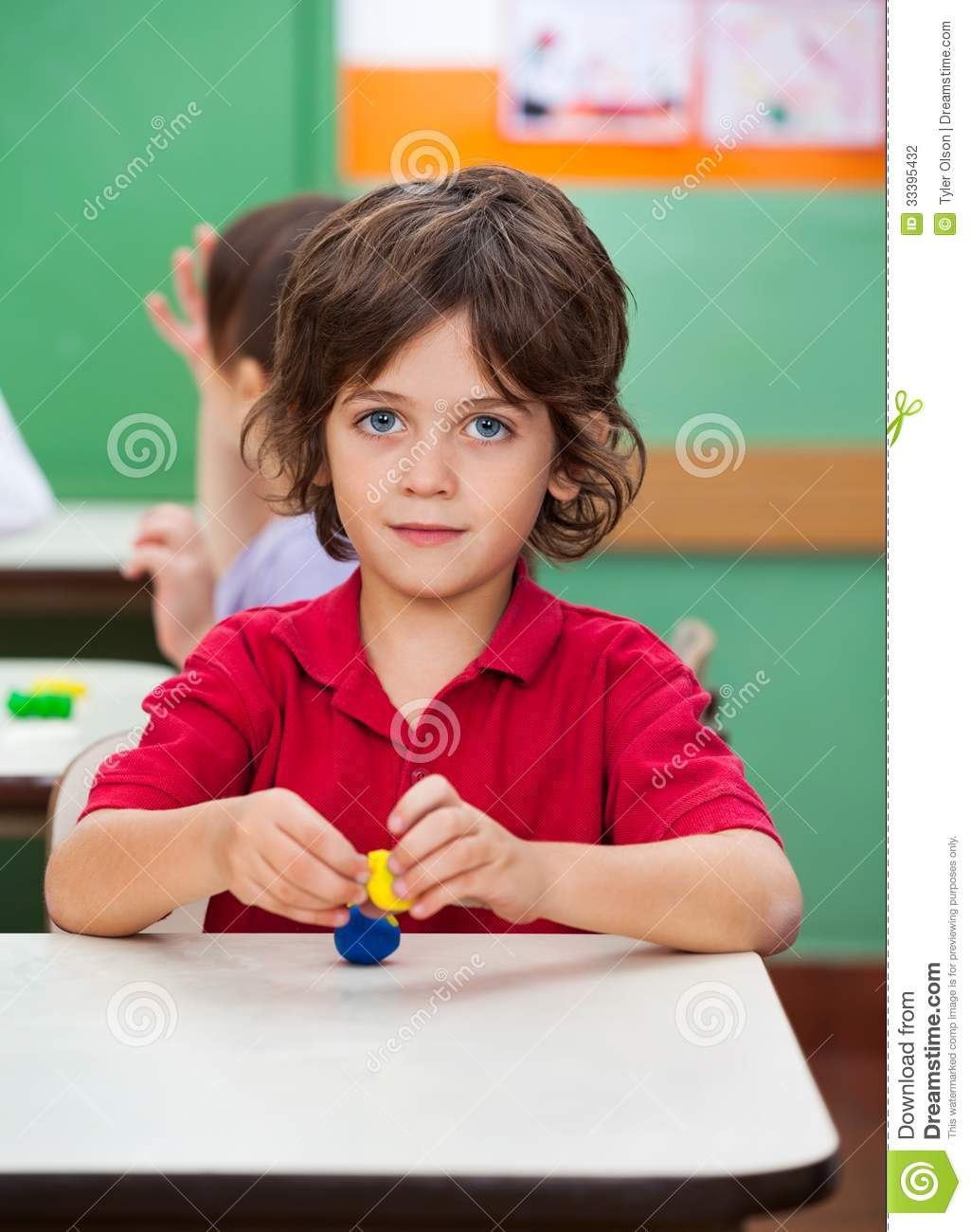 Boy Holding Clay Model At Desk Stock Photography - Image: 33395432