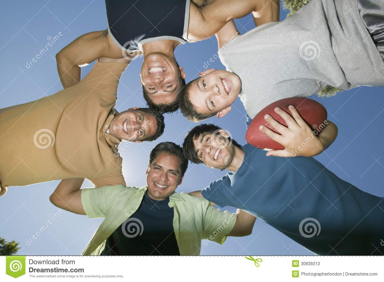 Boy (13-15) holding football with brothers and father in huddle view from below.