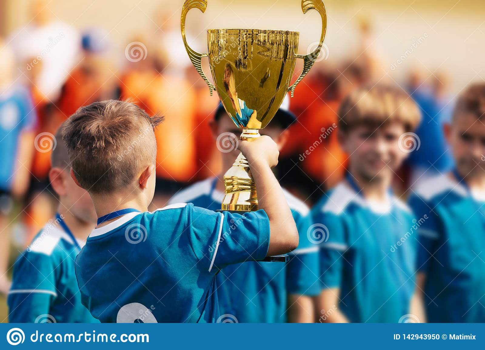 Boy holding golden trophy and celebrating sport success with team
