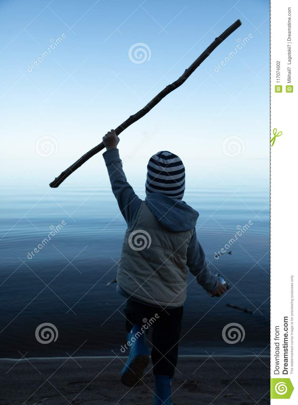 The boy runs to the water with a stick