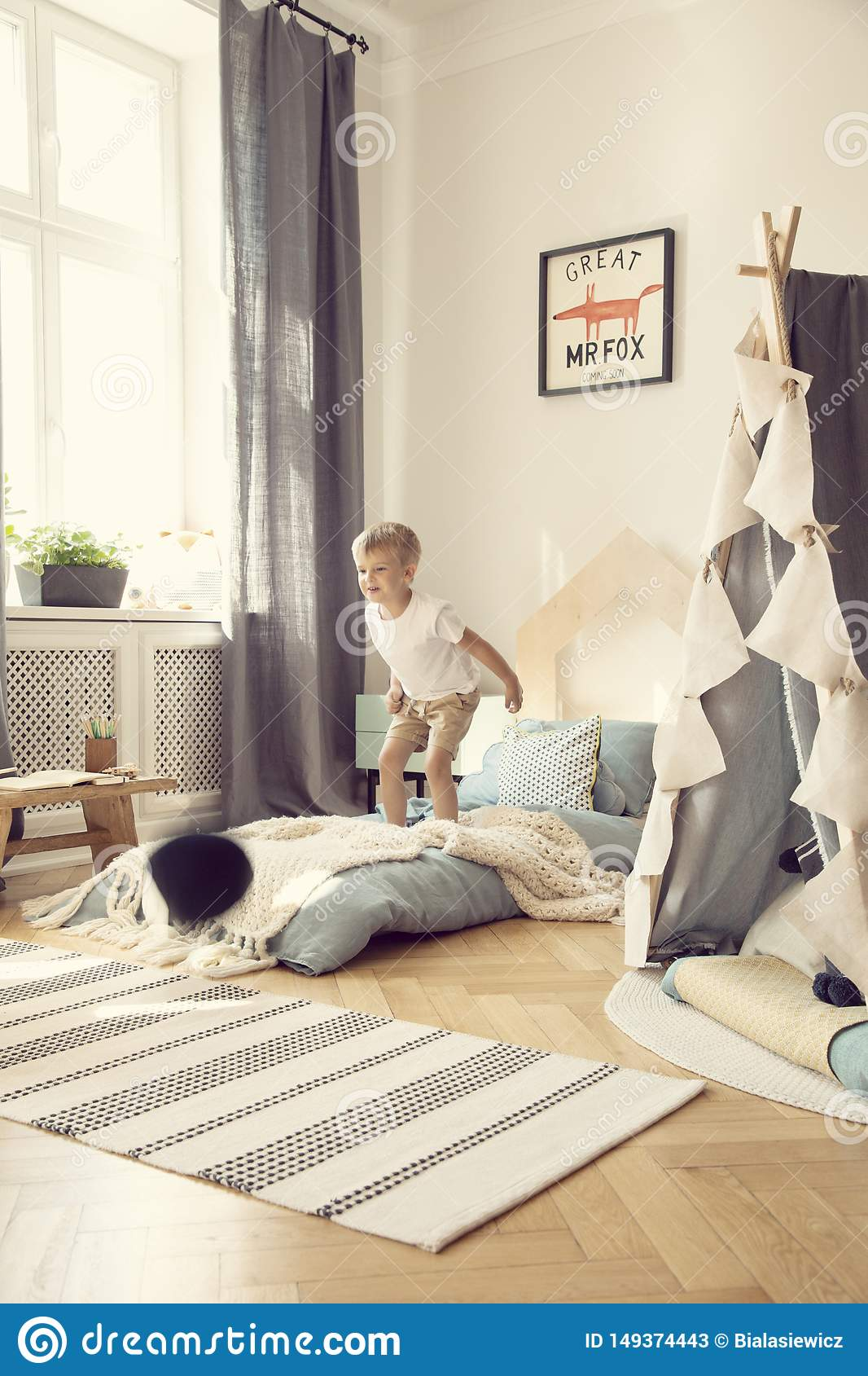 Boy Jumping On A Mattress In A Cozy Playroom Interior Stock Image Image Of Boho Floor 149374443