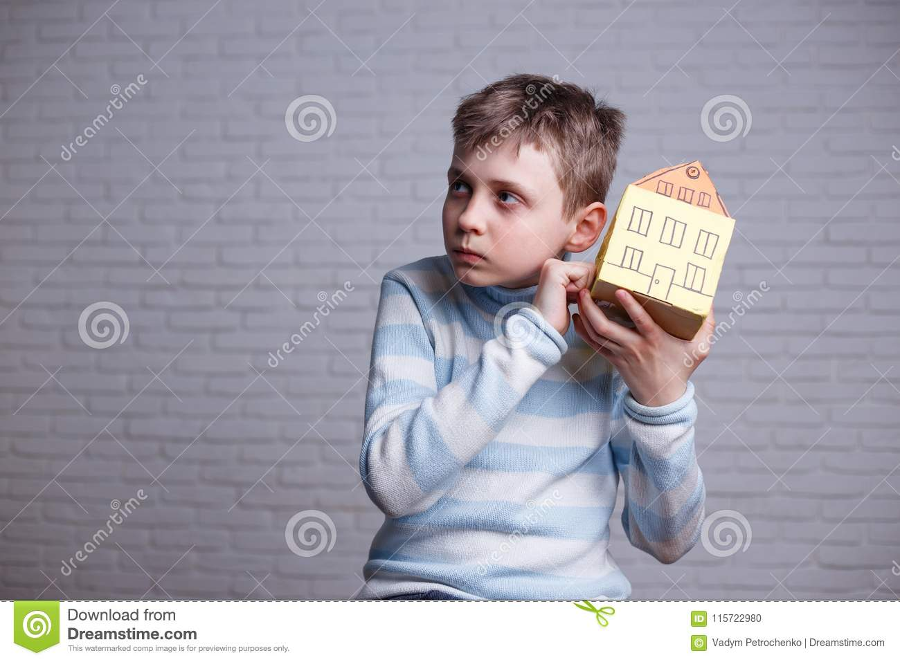 Boy knocking to cardboard toy house and listening. Teen and chil
