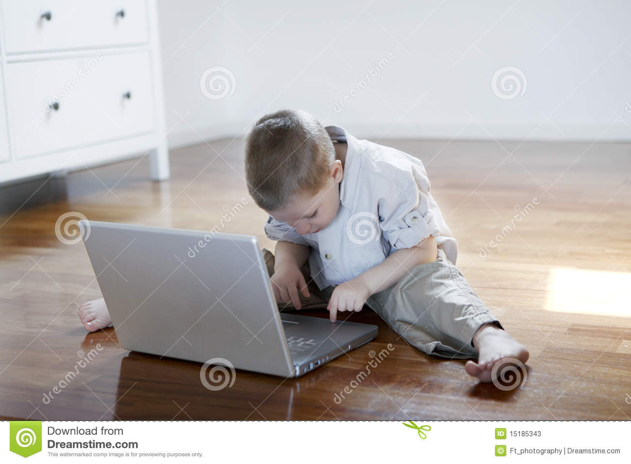 Boy on a laptop sitting down on the floor barefoot stock for Down to the floor