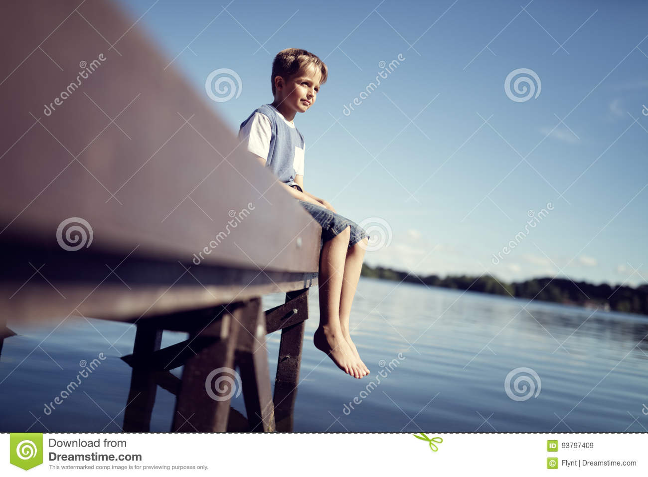 Boy with legs dangling from pier