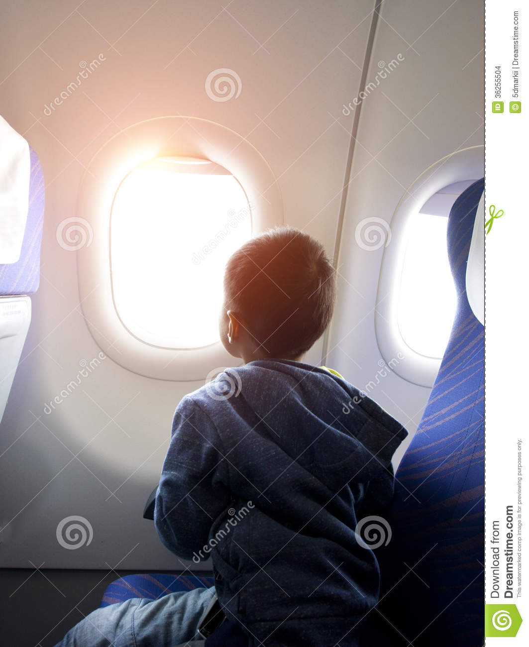 Boy Looking Outside Of Airplane Window Stock Photo