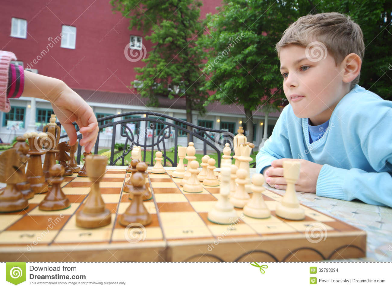 Boy looks like hand of girl moves chess piece on chessboard