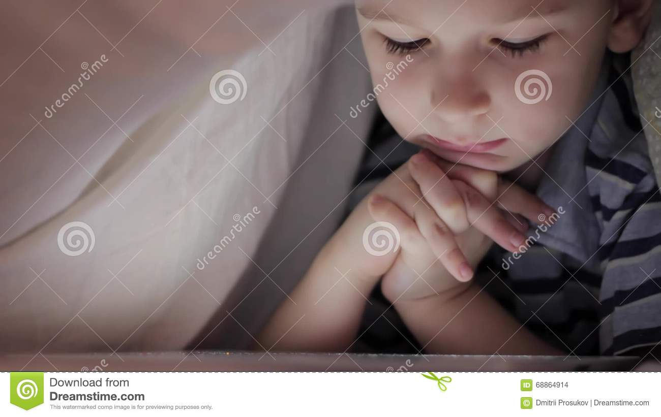 Boy Lying Under Blanket And Watching Cartoon On Touch Pad Stock ...