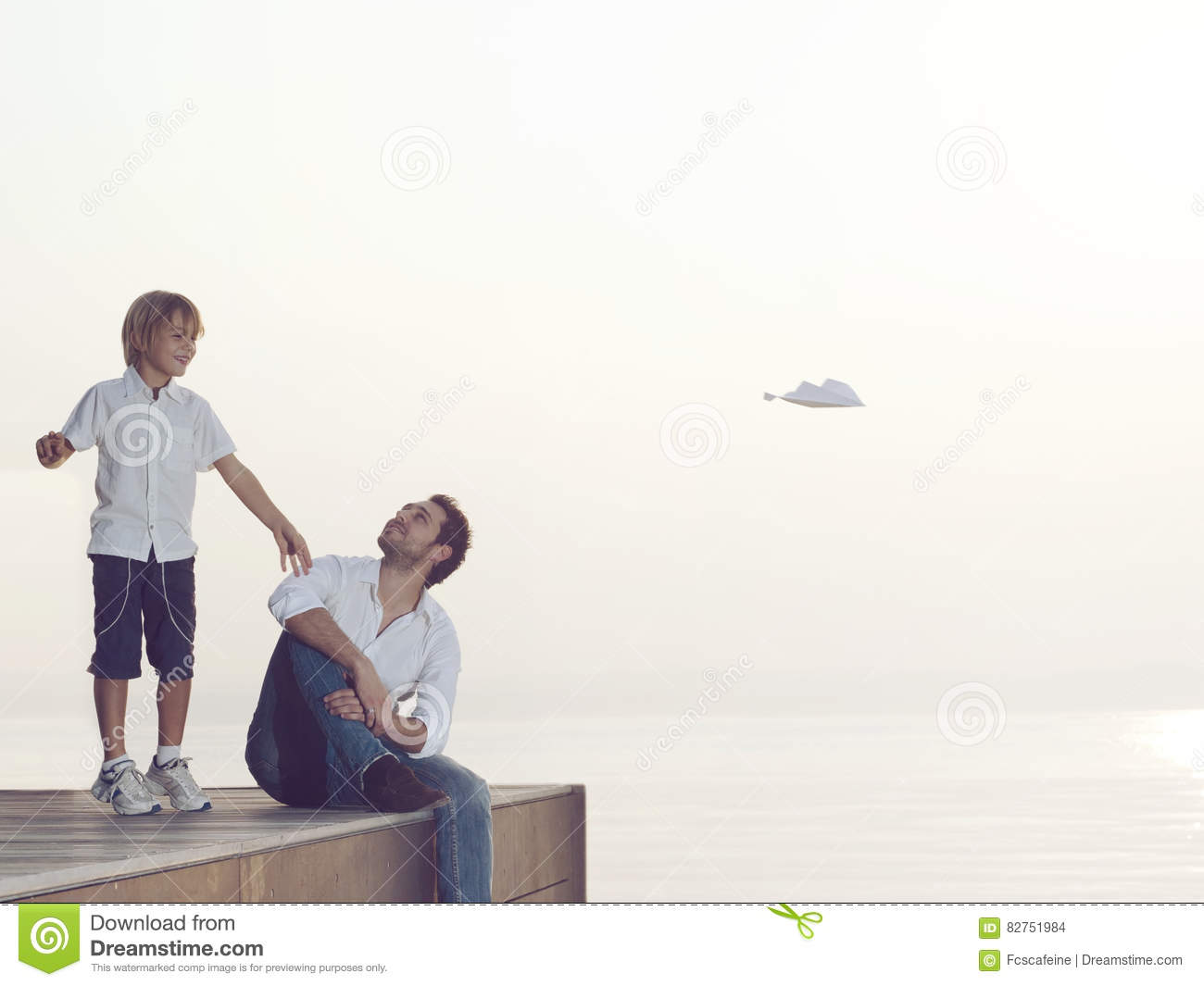 boy makes fly his paper airplane his father`s help stock boy makes fly his paper airplane his father`s help