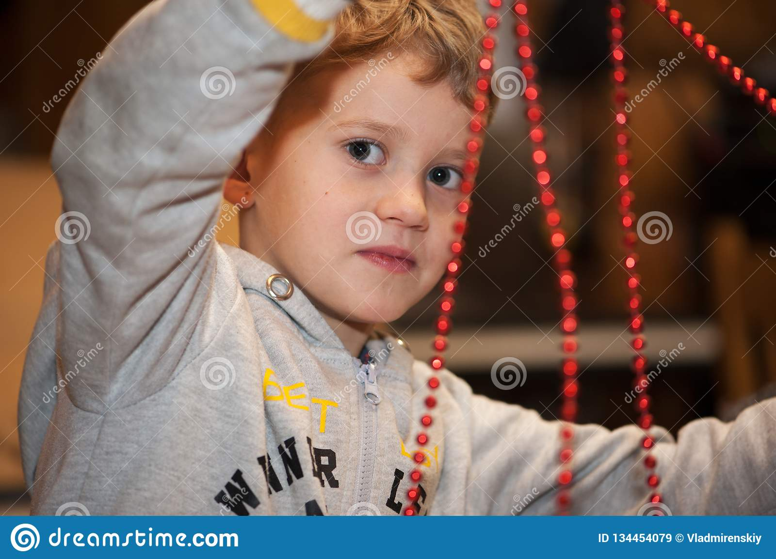 Boy making christmas decoration of red beads