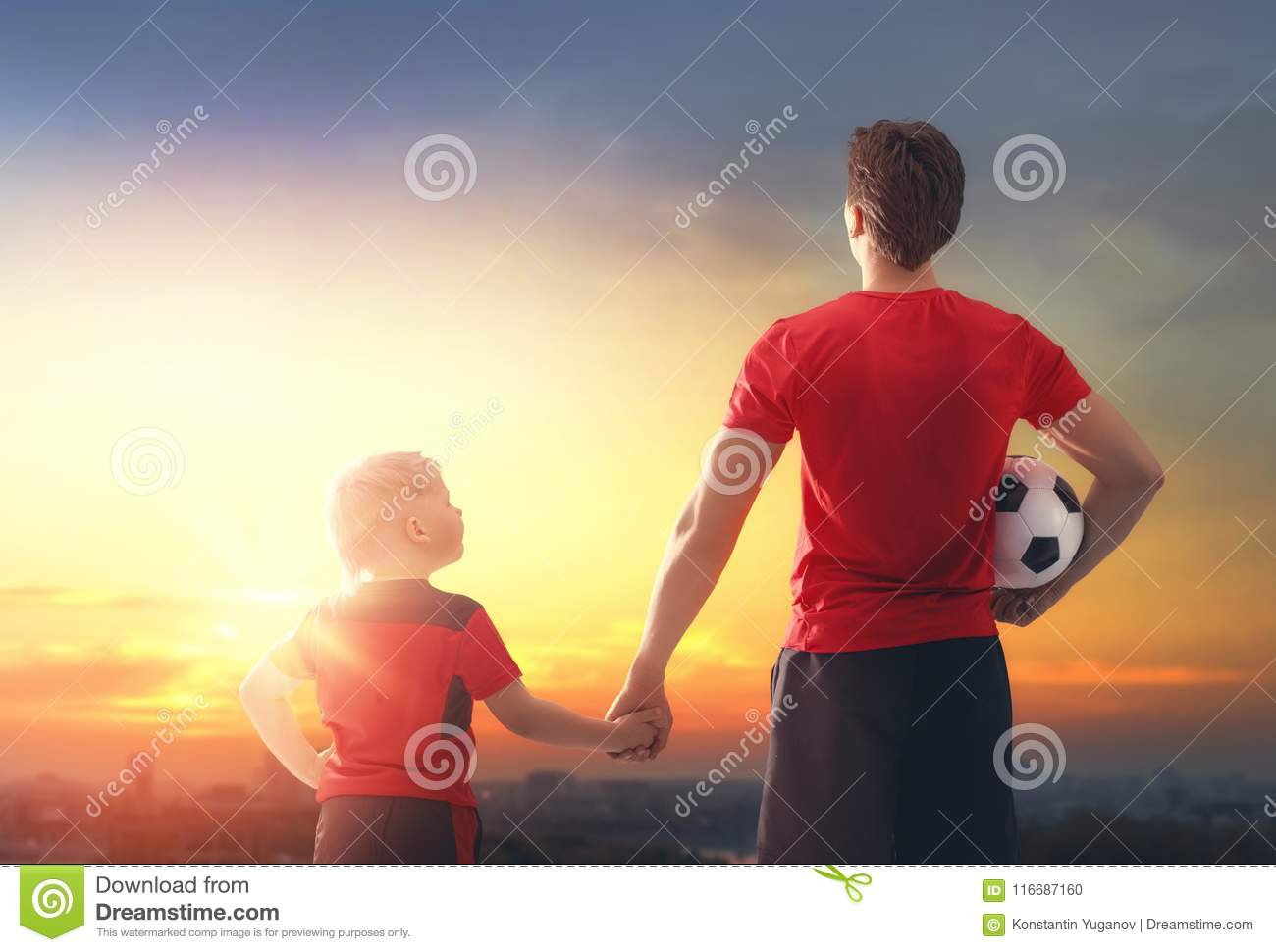 Boy with man playing football