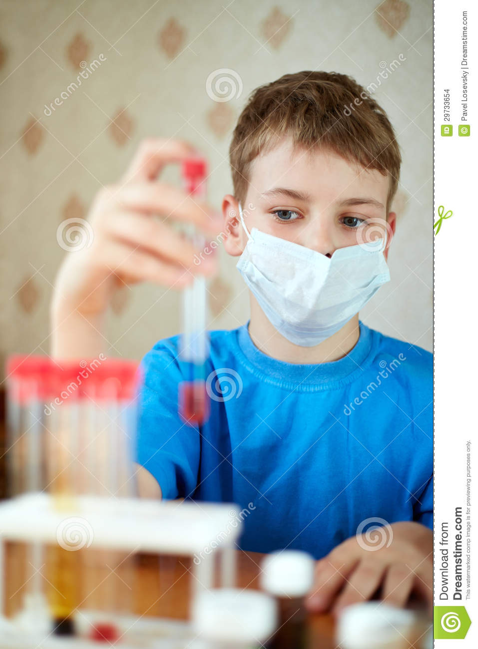Boy in mask-respirator sits at table with chemical reagents