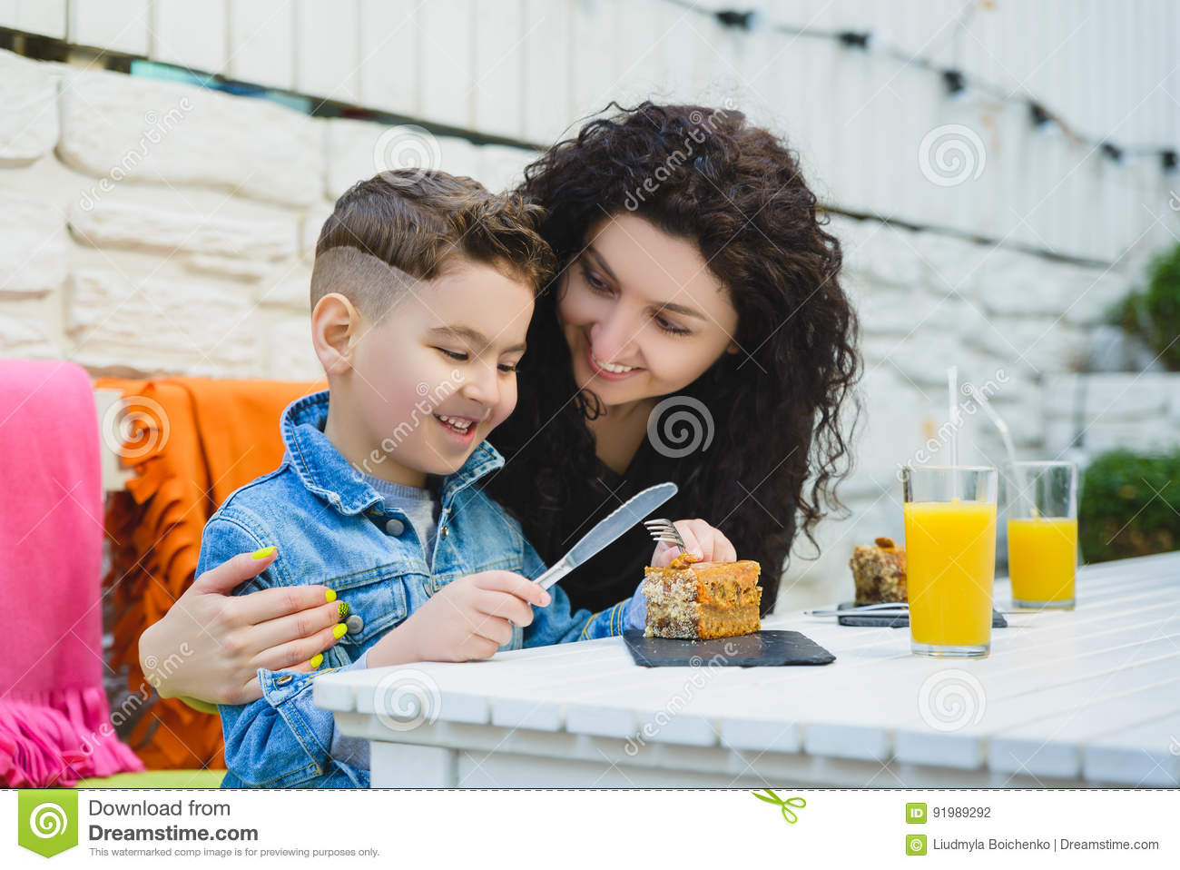 Boy and mother or happy family having healthy breakfast in resort cafe outdoor