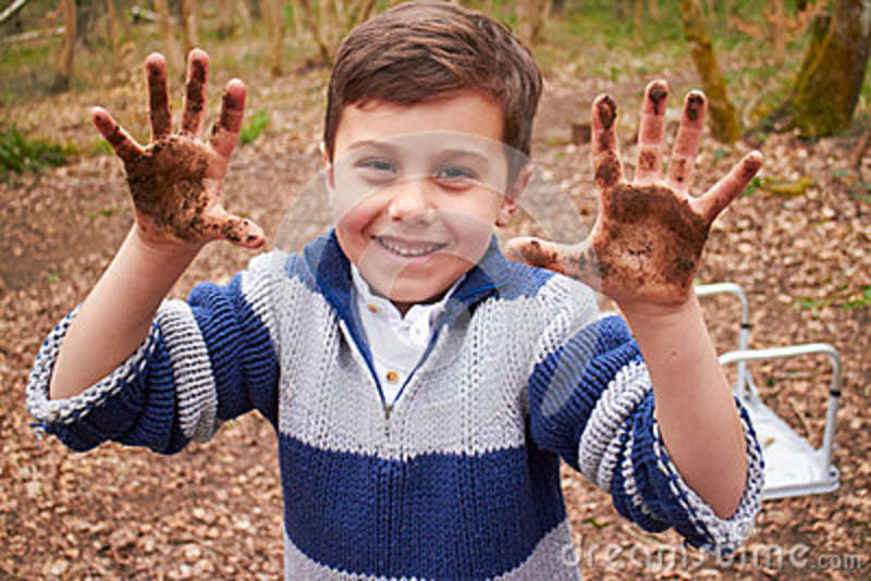 Boy With Muddy Hands Playing In Forest