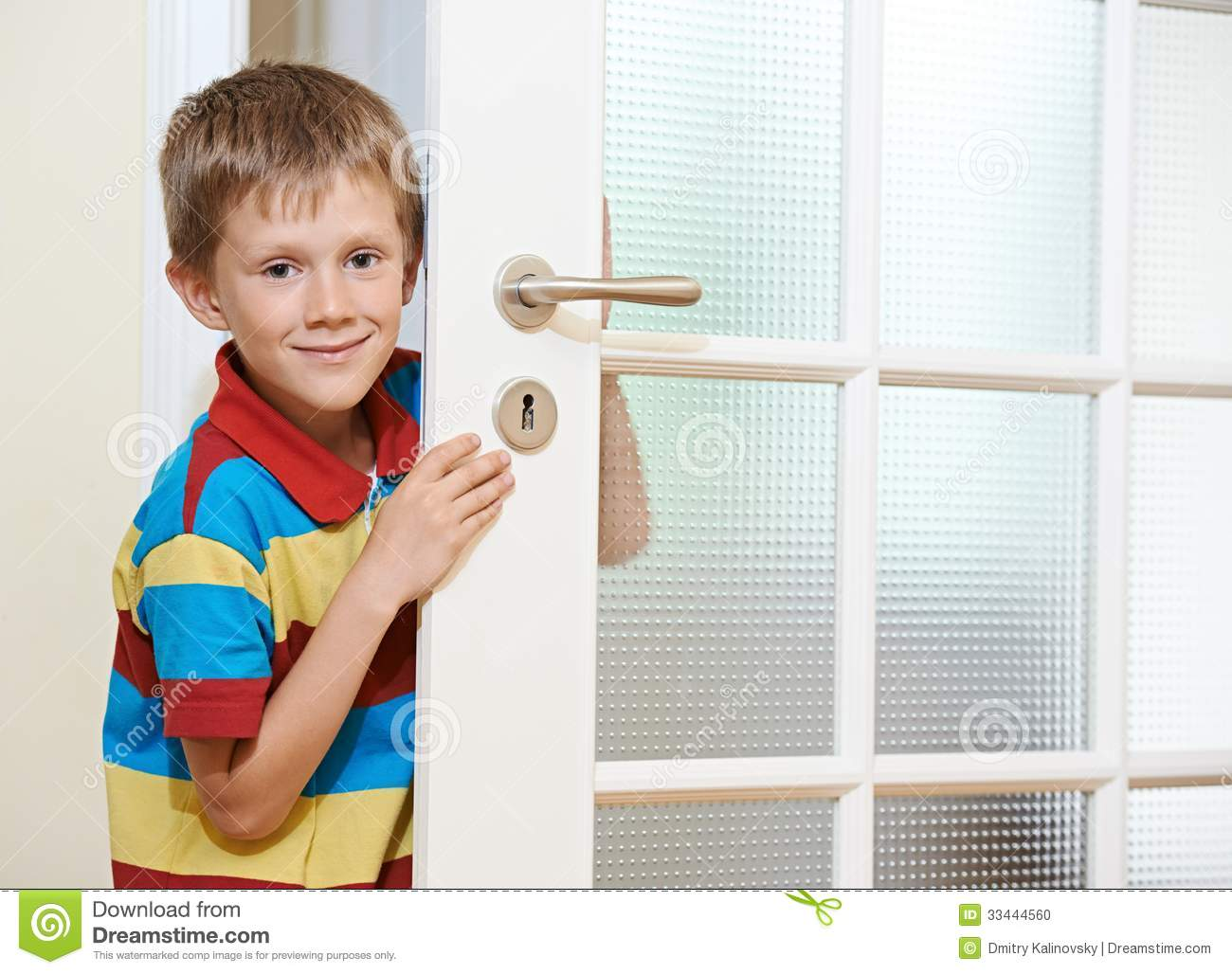 Little smiling boy opening the white door at home.