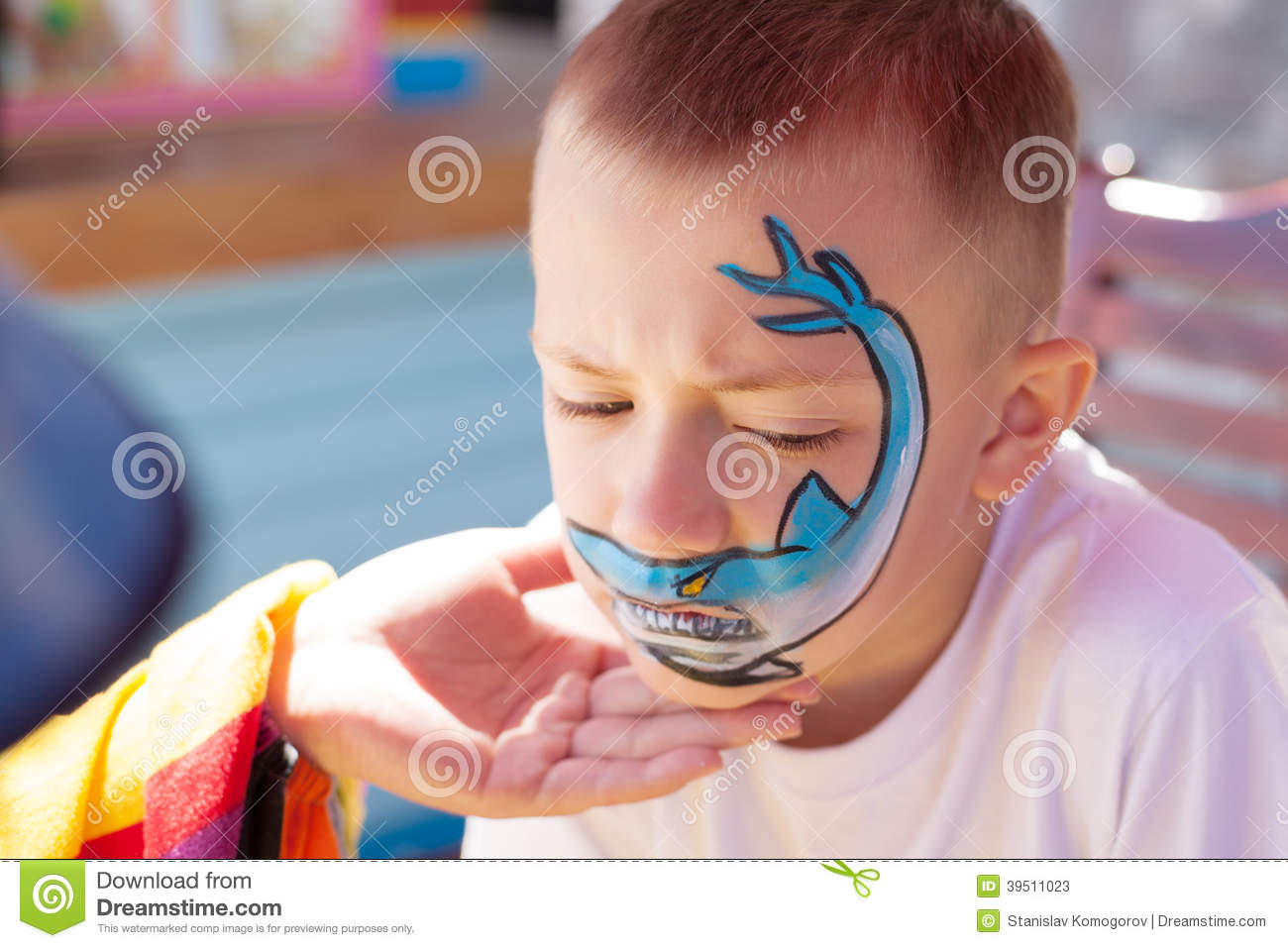 Boy painting face with shark.
