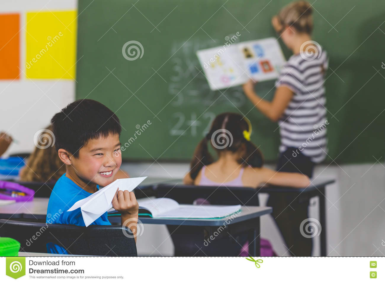 Boy with a paper plane while teacher teaching in classroom