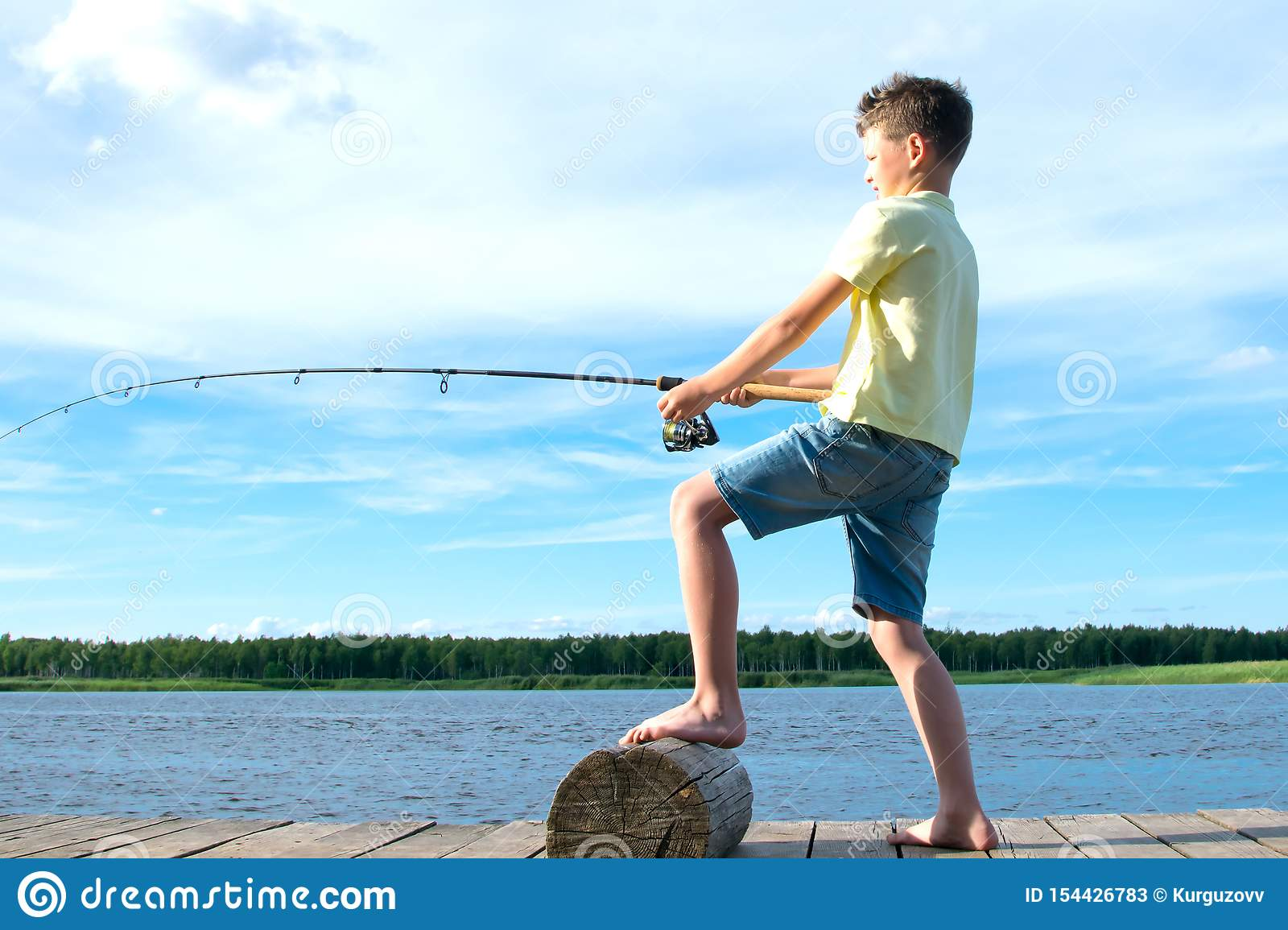The boy on the pier, against the blue lake and the sky,pulls the catch on a fishing rod