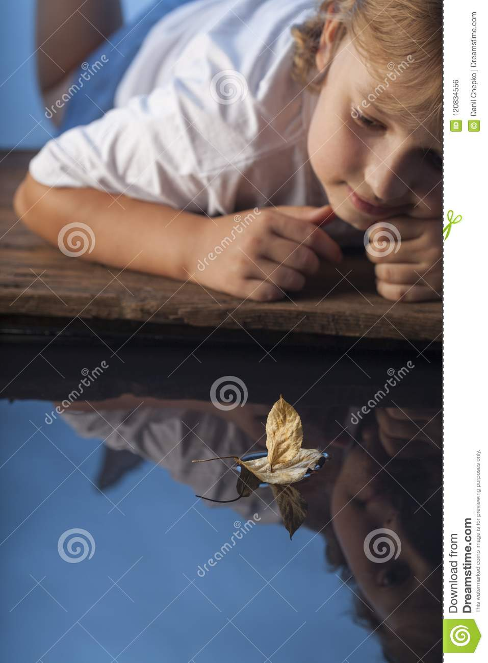 Boy play with leaf ship in water