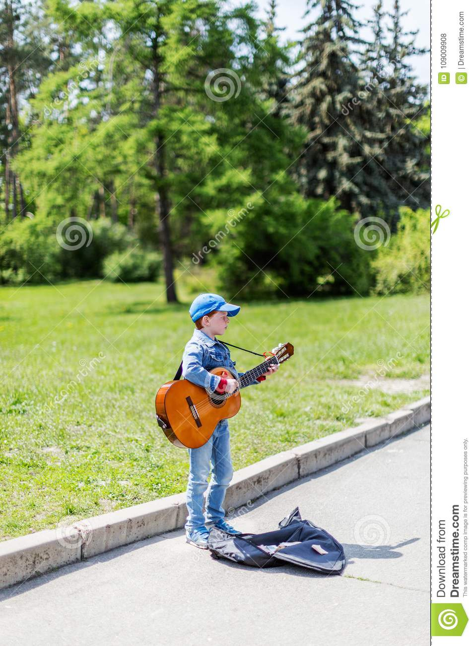 Boy playing on acoustic guitar outdoors. Little street musician. KYIV UKRAINE May 01, 2016