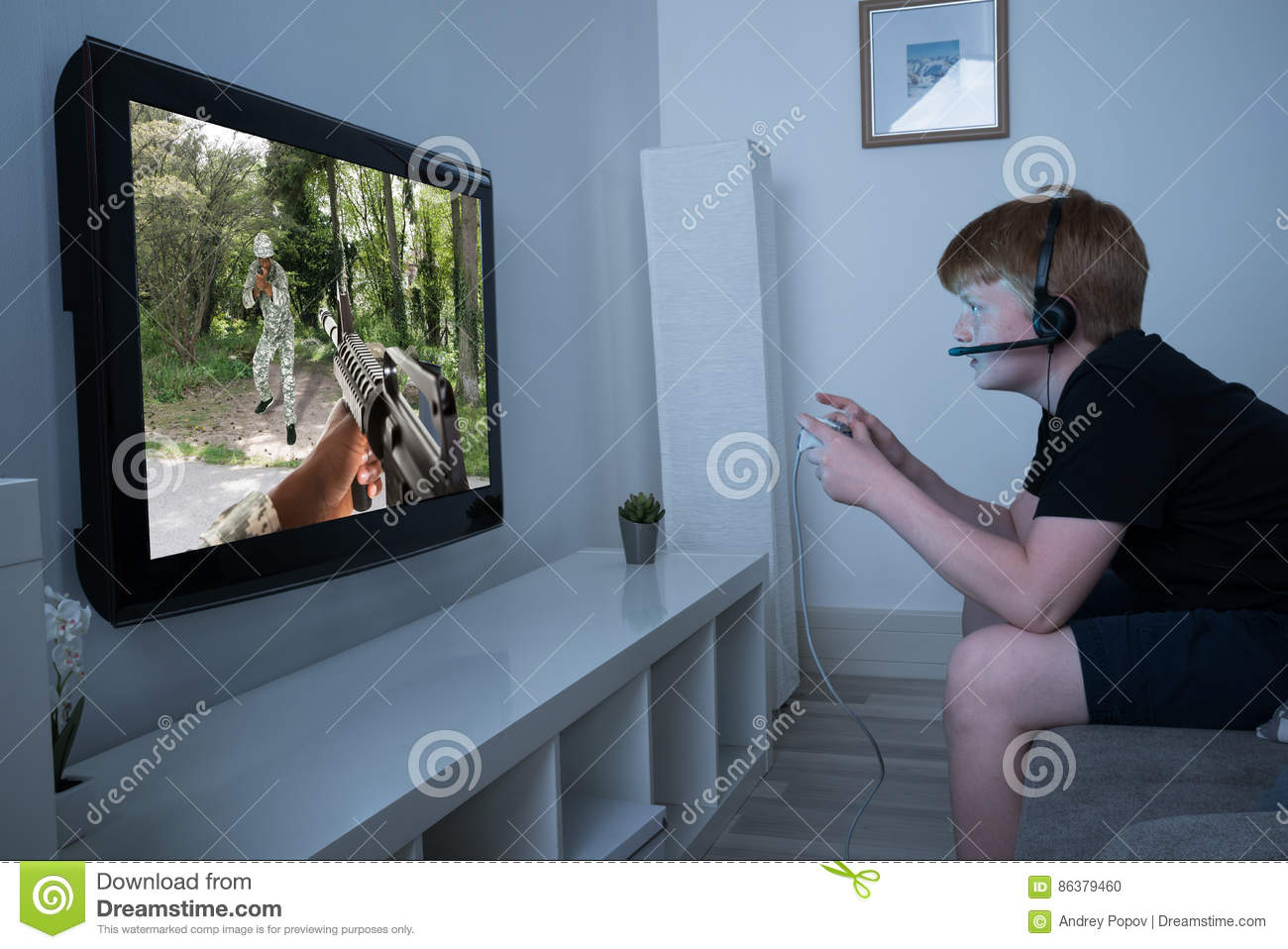 Boy Playing Action Game On Television