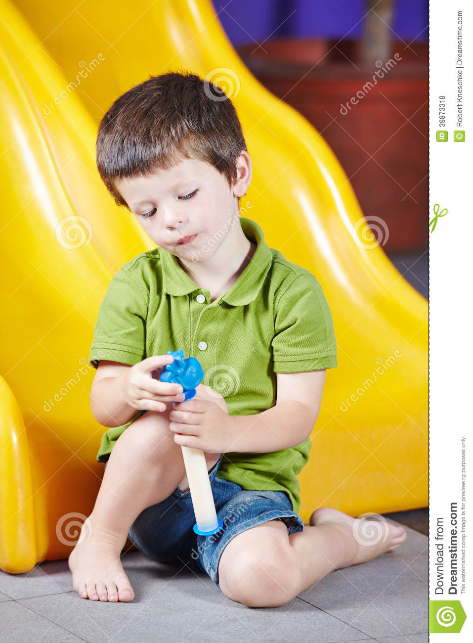 Boy Playing Alone In Kindergarten Stock Photo