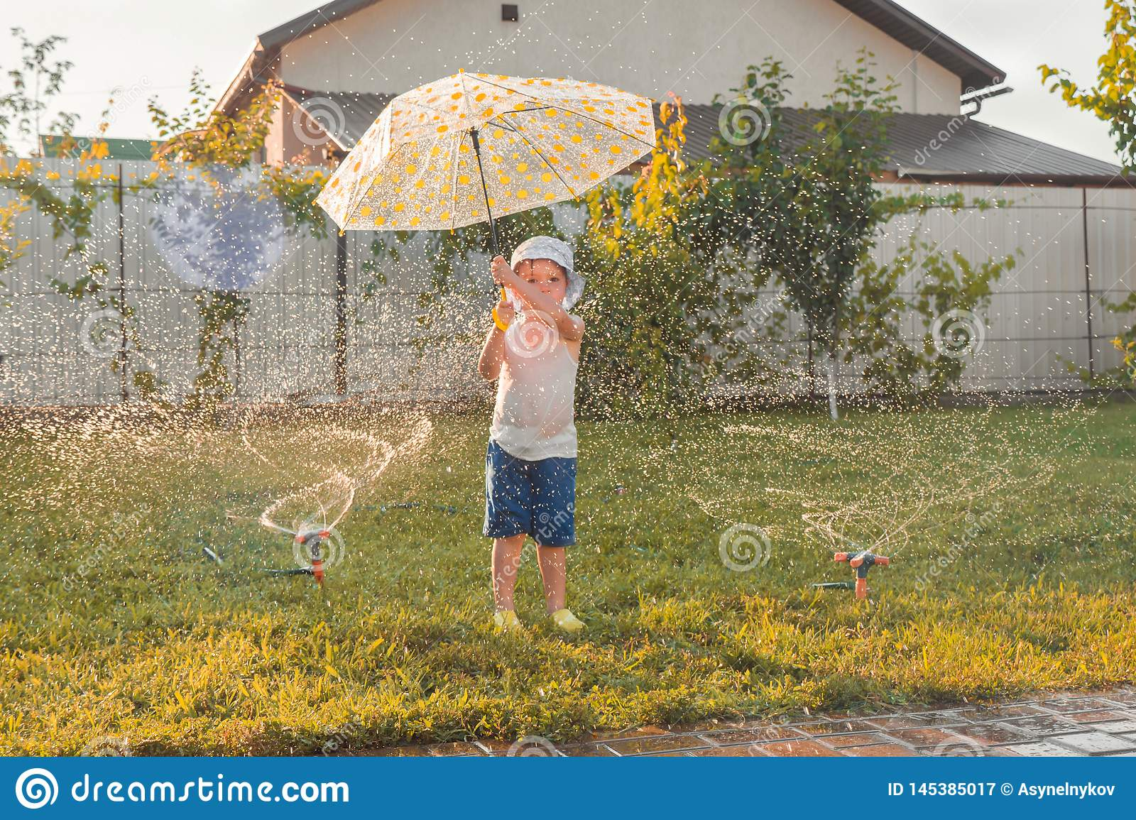 Summer activities. Children playing outdoor. Happy boy playing outdoor with watering system. Summer vacation. Summer