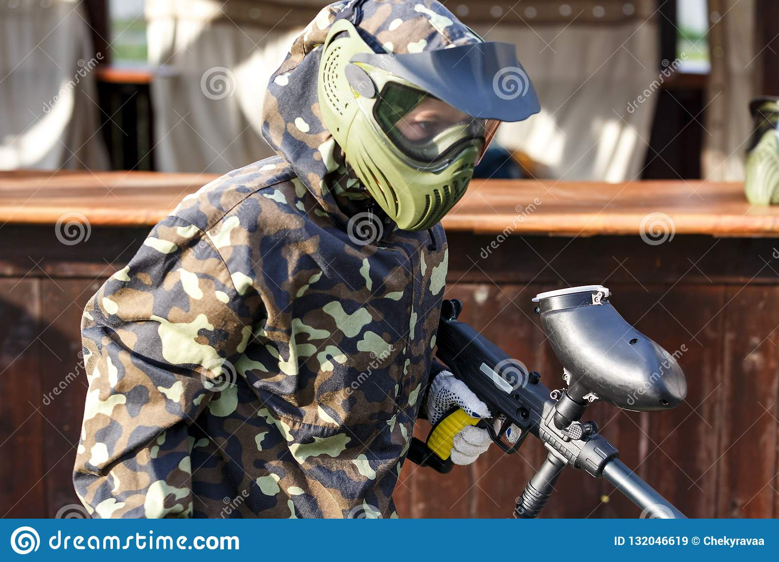 Boy is playing paintball on the field. paintball games can be played on indoor or outdoor fields