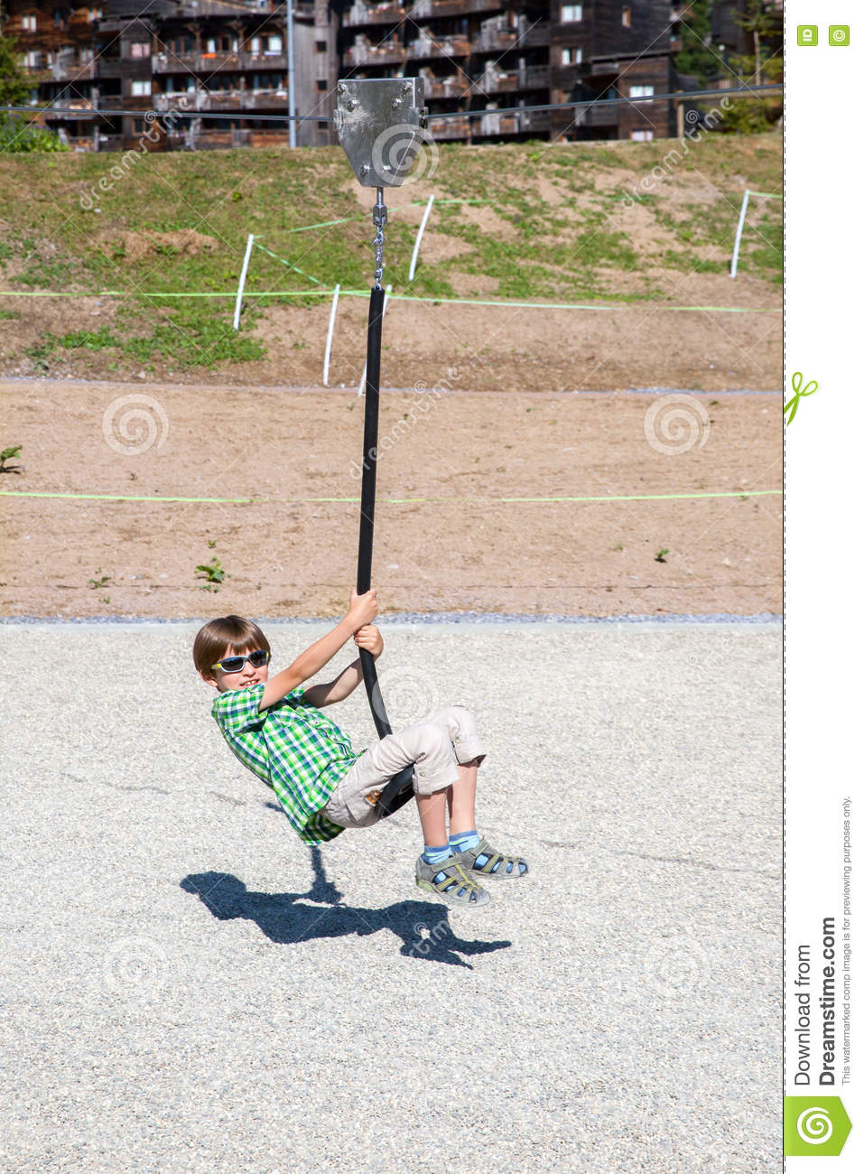 A boy is playing with rope swing on playground stock photo for Rope swing plans