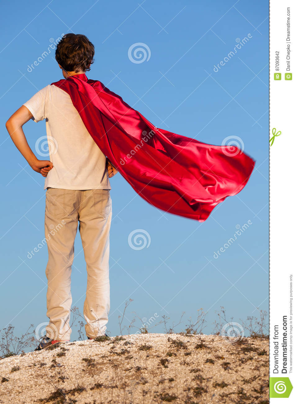 Boy playing superheroes on the sky background,