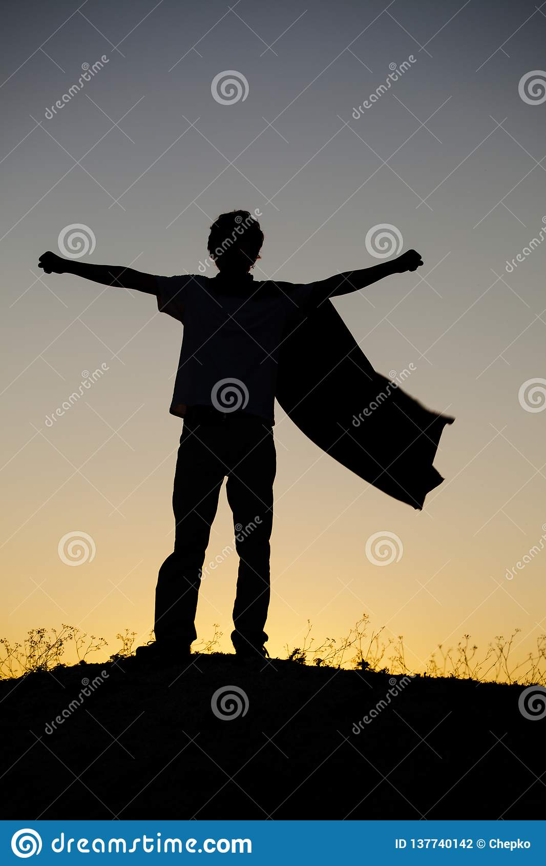 Boy playing superheroes on the sky background, teenage superhero in a red cloak on hill