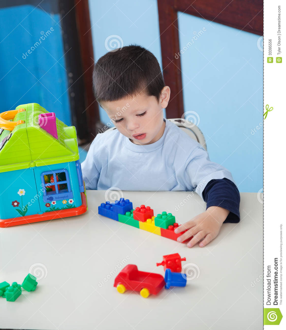 Toys For Boys Kindergarten : Boy playing with toys at desk in preschool royalty free