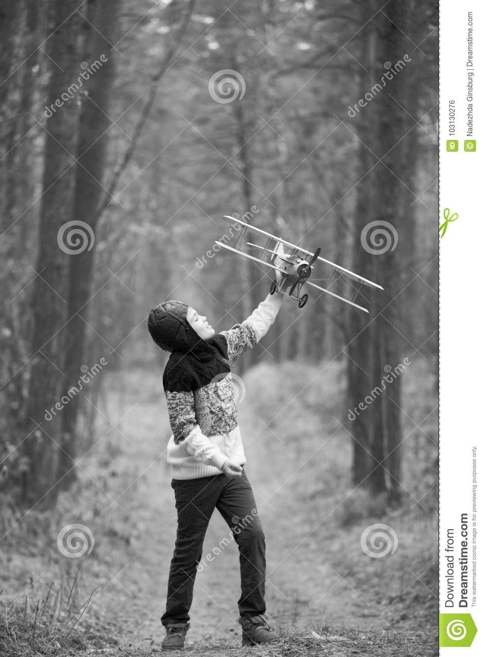 185e6e02 A Boy Plays In The Woods With A Toy Plane. Autumn Games In The W ...