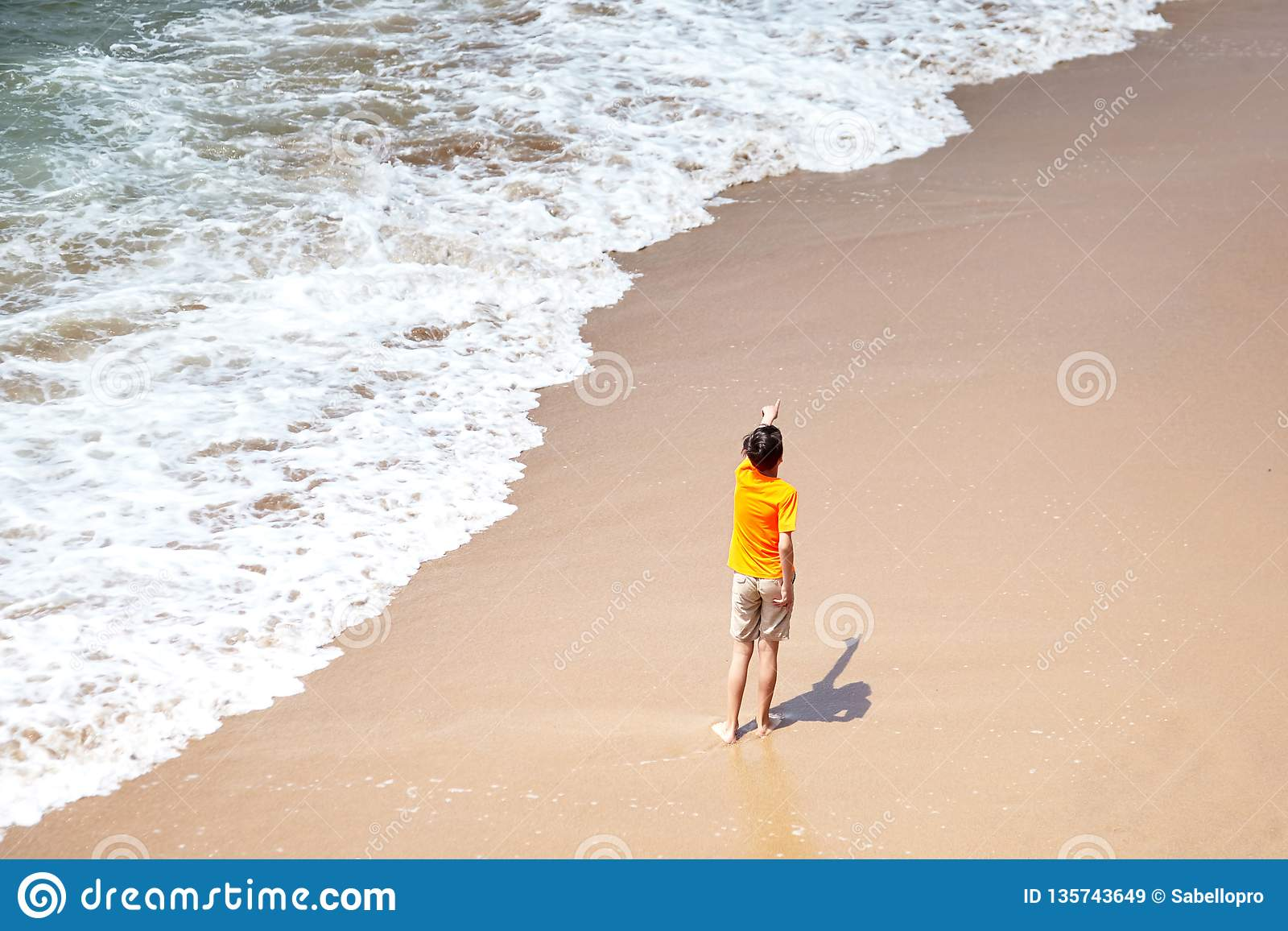 Boy pointing his hand away, kid playing on a sandy beach by the sea water
