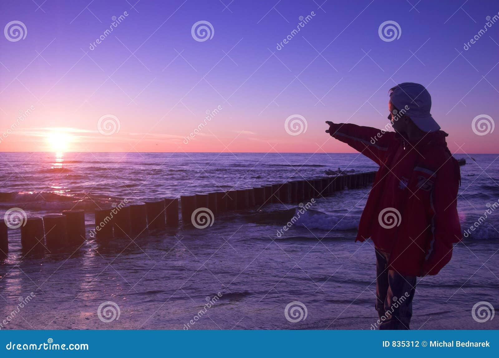 Boy pointing to sun