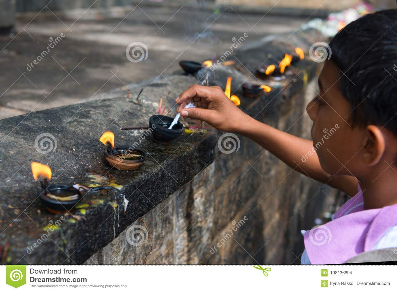 Boy prepares oil lamp to set fire it in an offerings place of th