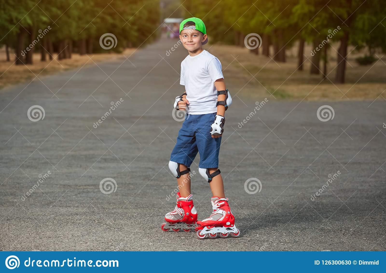The boy put on protective knee pads and skates in the park