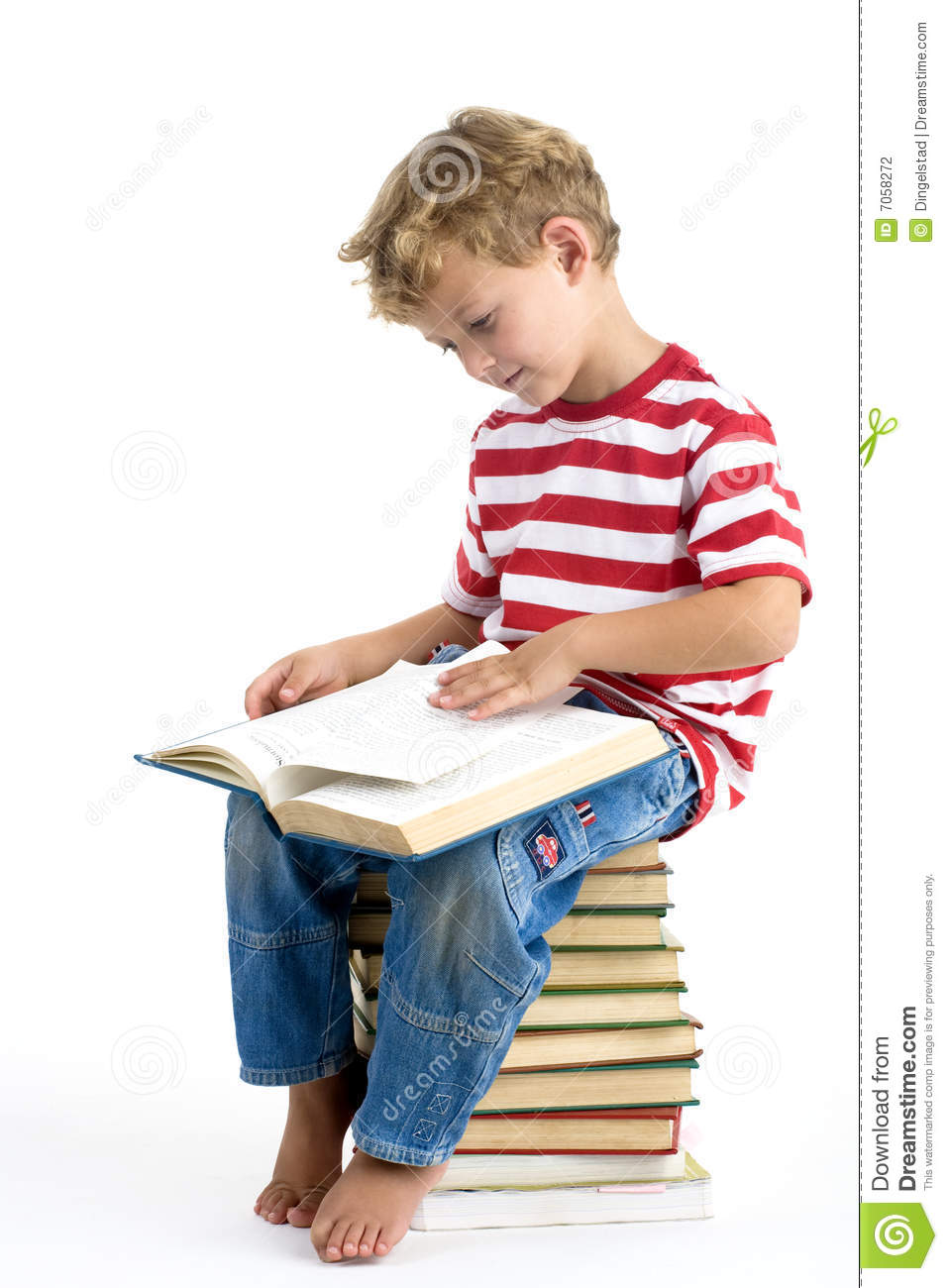 Five year old boy sitting on pile of books, reading.