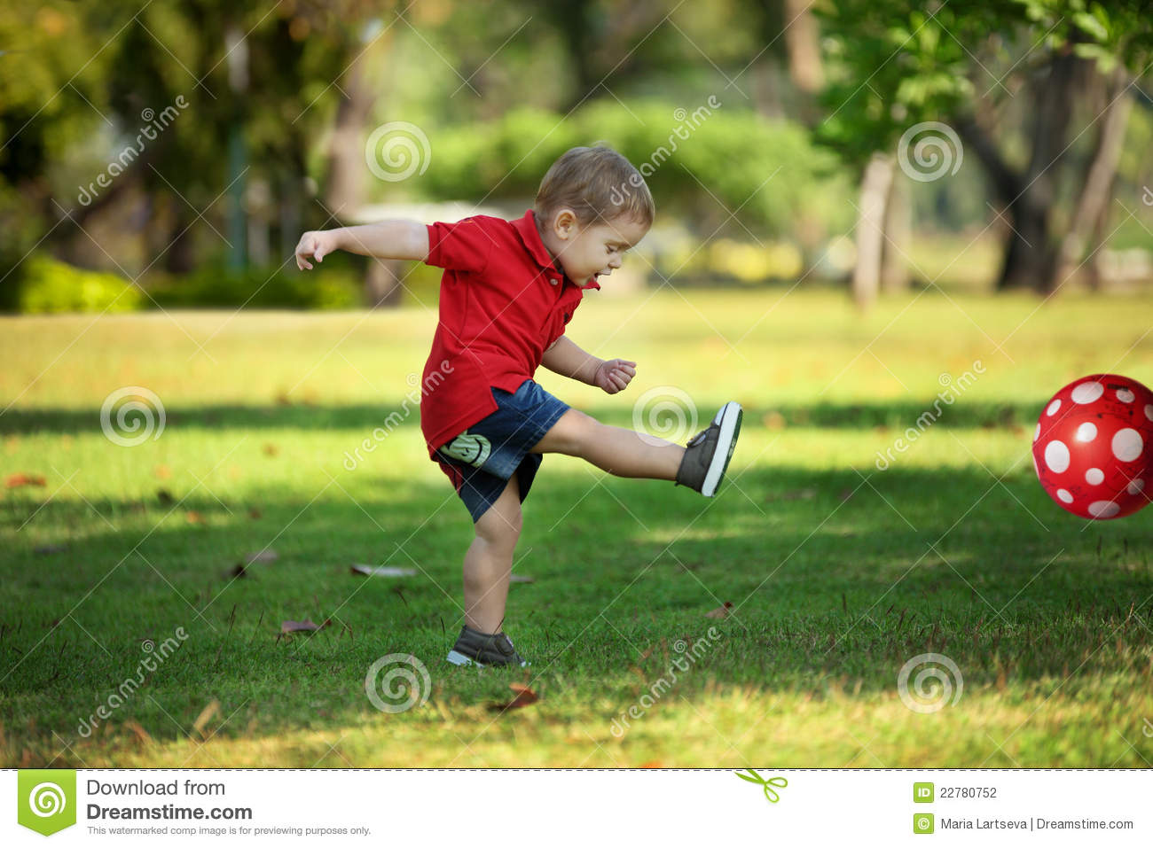 Infant boy in red shirt kicking red football out of frame in park.