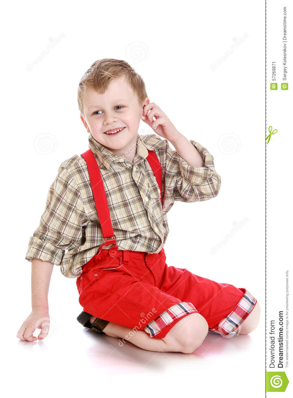 7c80d72b1 Joyful blond little boy plaid shirt long sleeve long bright red shorts  sitting on his knees on the floor. Boy hand touches his ear and looks  aside-Isolated ...