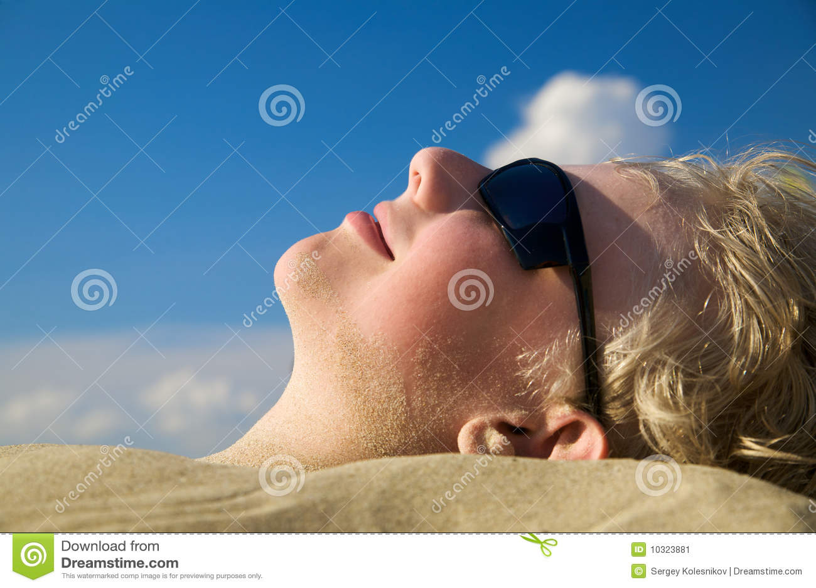 Boy relaxing on summer beach in sunglasses