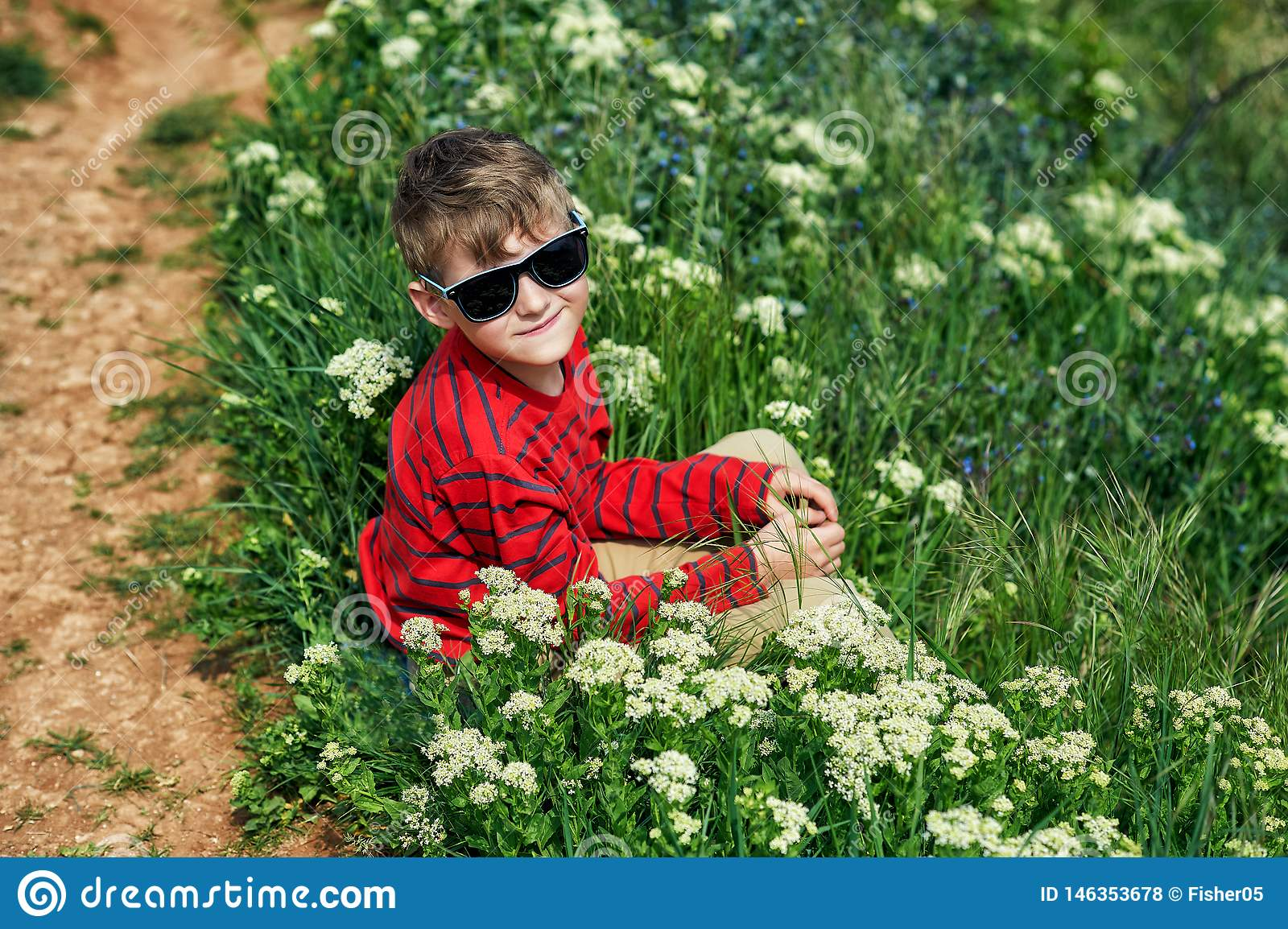 Boy resting sitting on the grass during a country walk