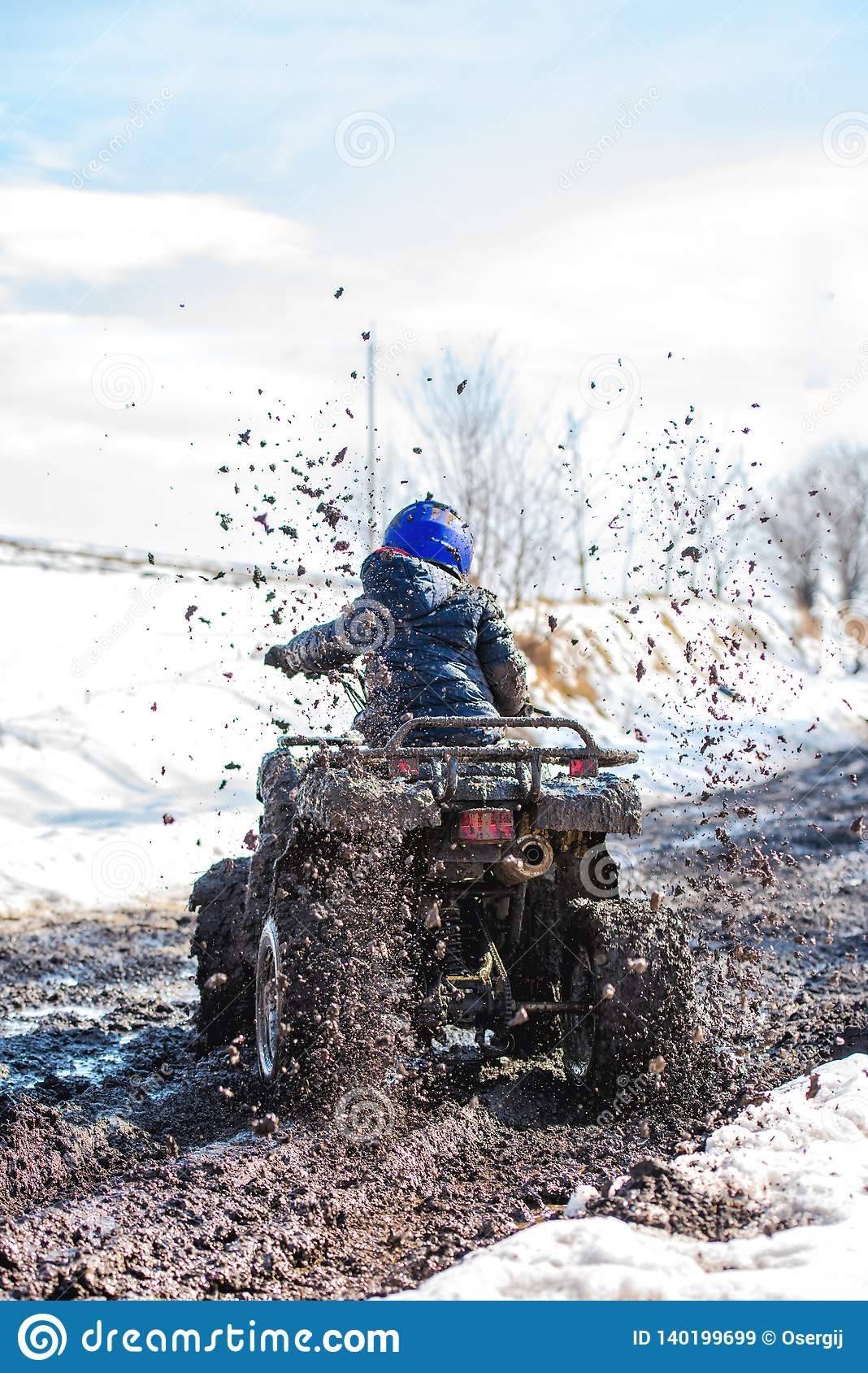 The boy is riding an ATV off-road