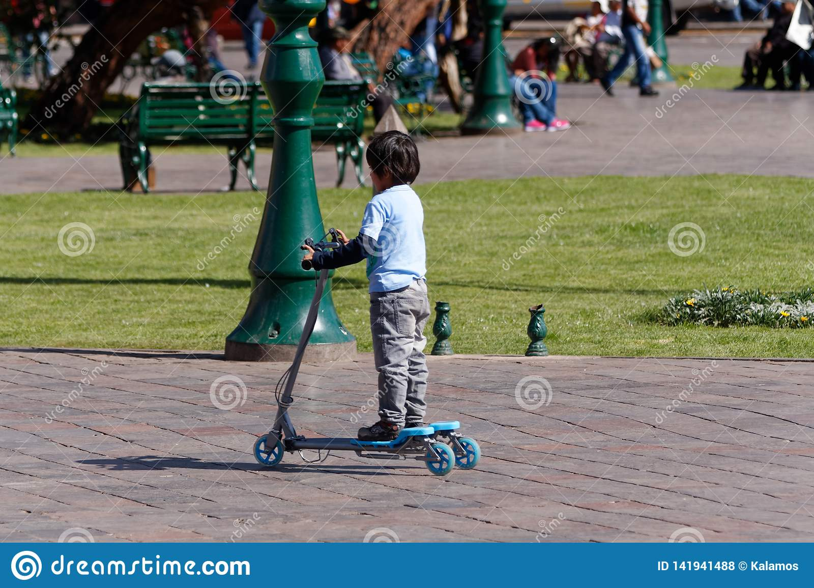 A boy riding his scooter