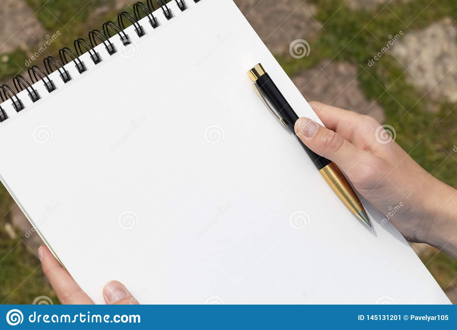 Boy`s hand with a pencil over an open notepad in the park