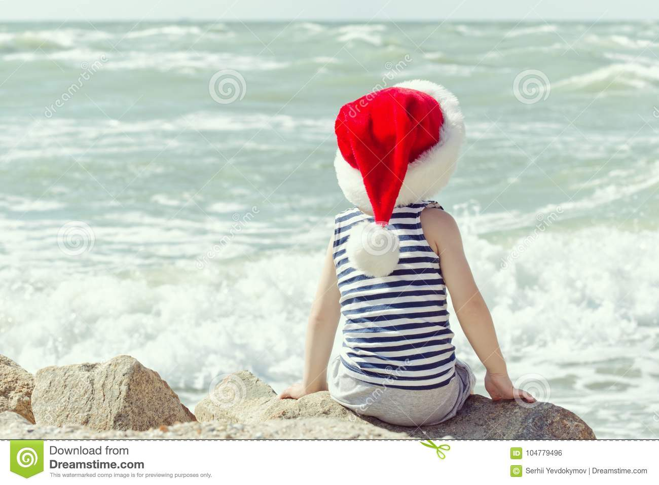 900f26b0bfb Boy In Santa Hat Sitting On A Rock. Sea Shore. Back View Stock Photo ...