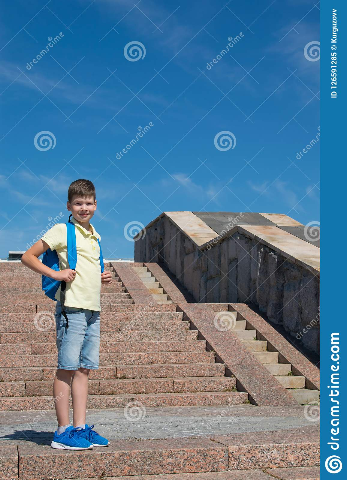 Boy with a school bag stands tall against a blue sky, to the right of the stairs. A boy with a school bag stands tall against a blue sky, to the right of the Royalty Free Stock Photo