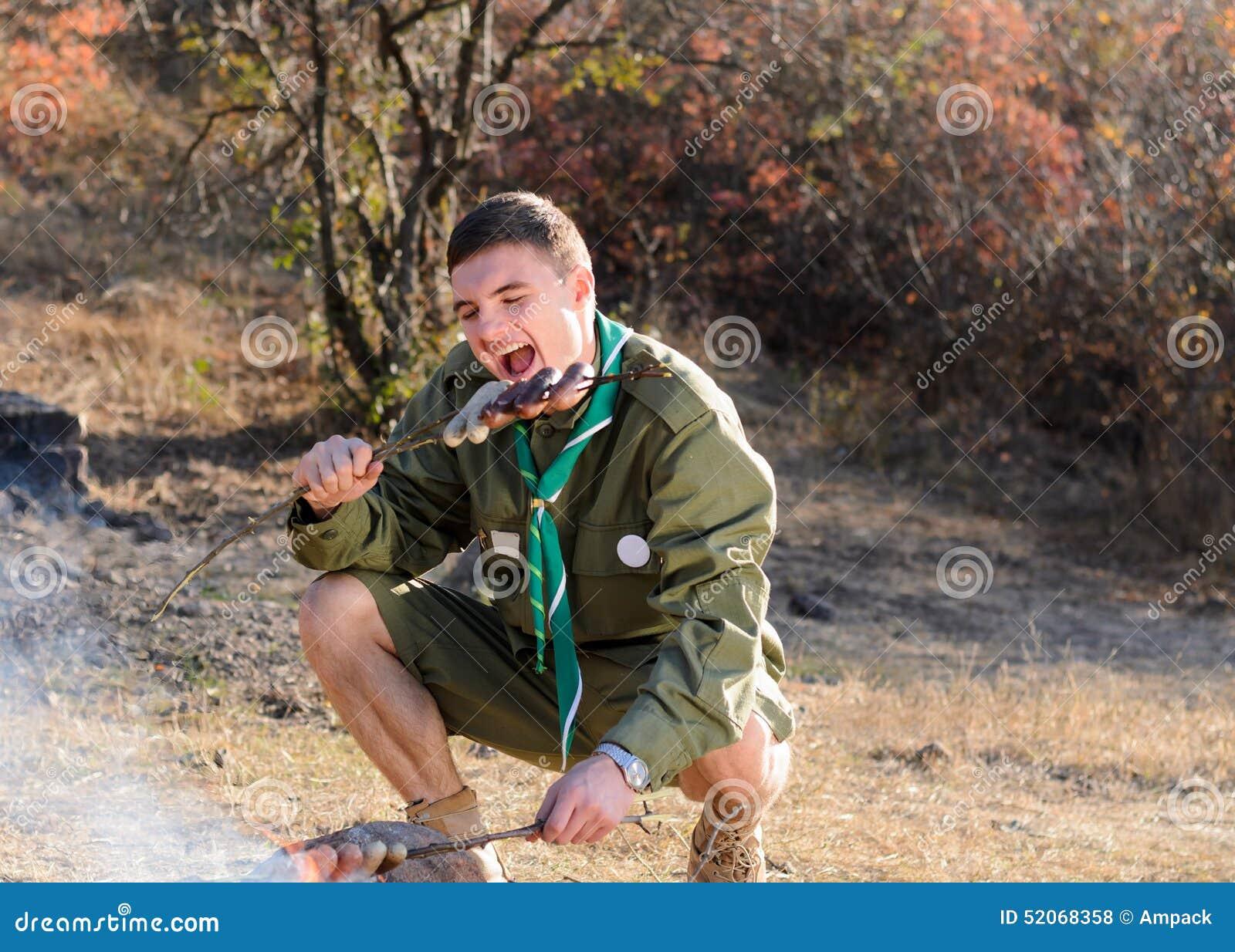 Boy scout Eating Sausage en el palillo por la hoguera