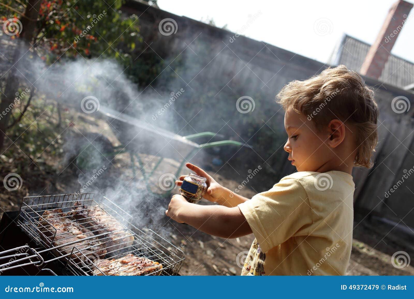 Boy Seasoning Pork Chops With Pepper Stock Image - Image of