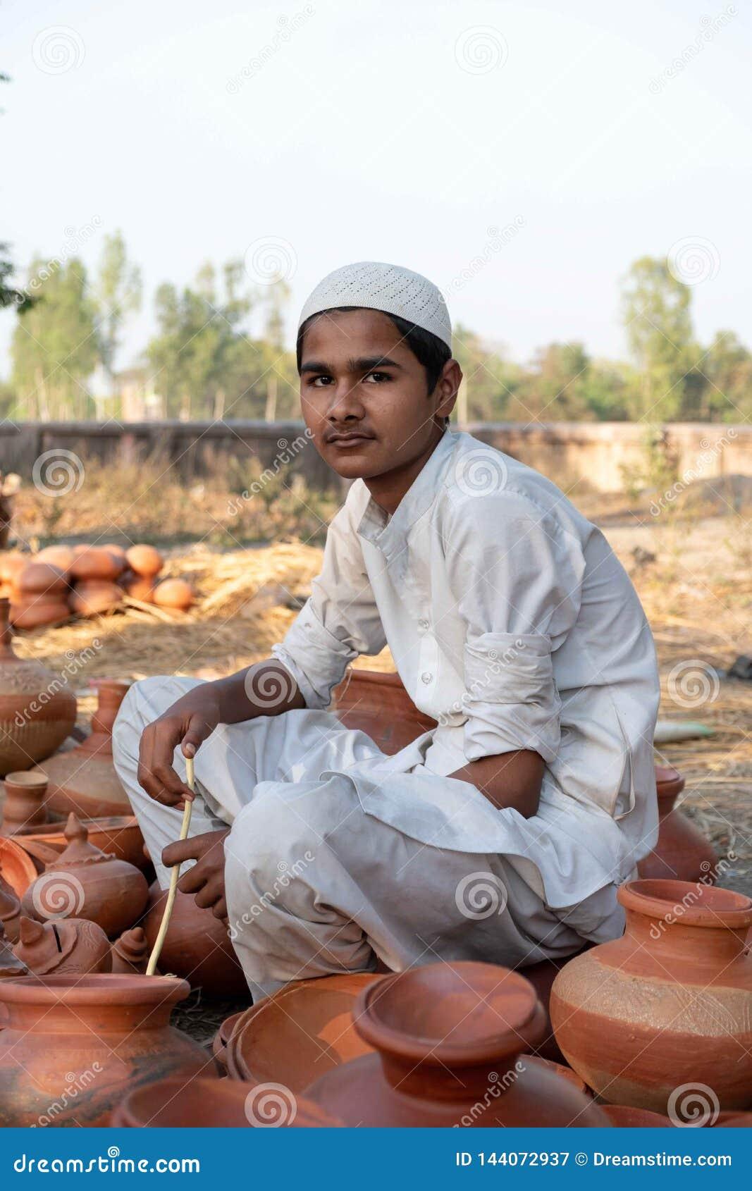 Bhadarsa, Uttar Pradesh/India-April 3,2019: A boy selling pottery poses for a photo at a festival surrounding Nandigram Bharatkund