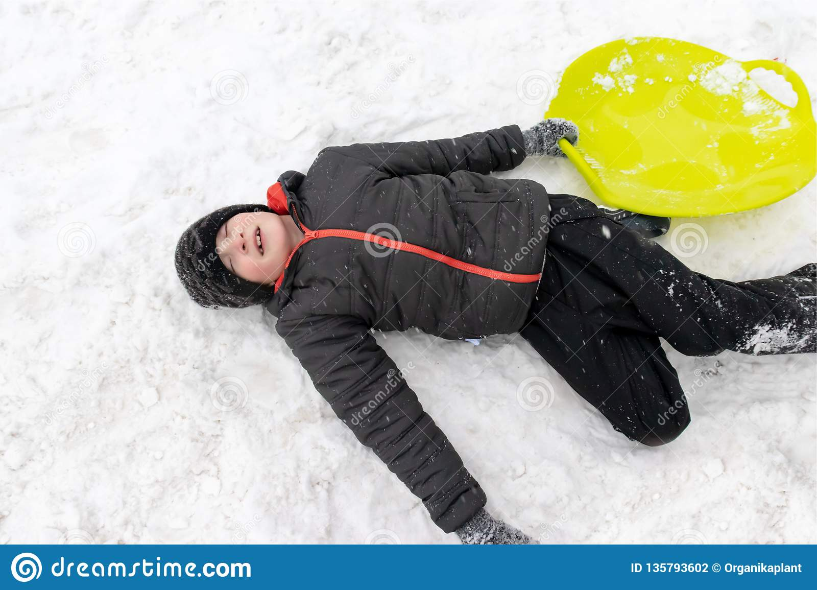 A boy of seven years old lying on the snow and holding a green plastic sled in his hand. Concept of winter activities, recreation